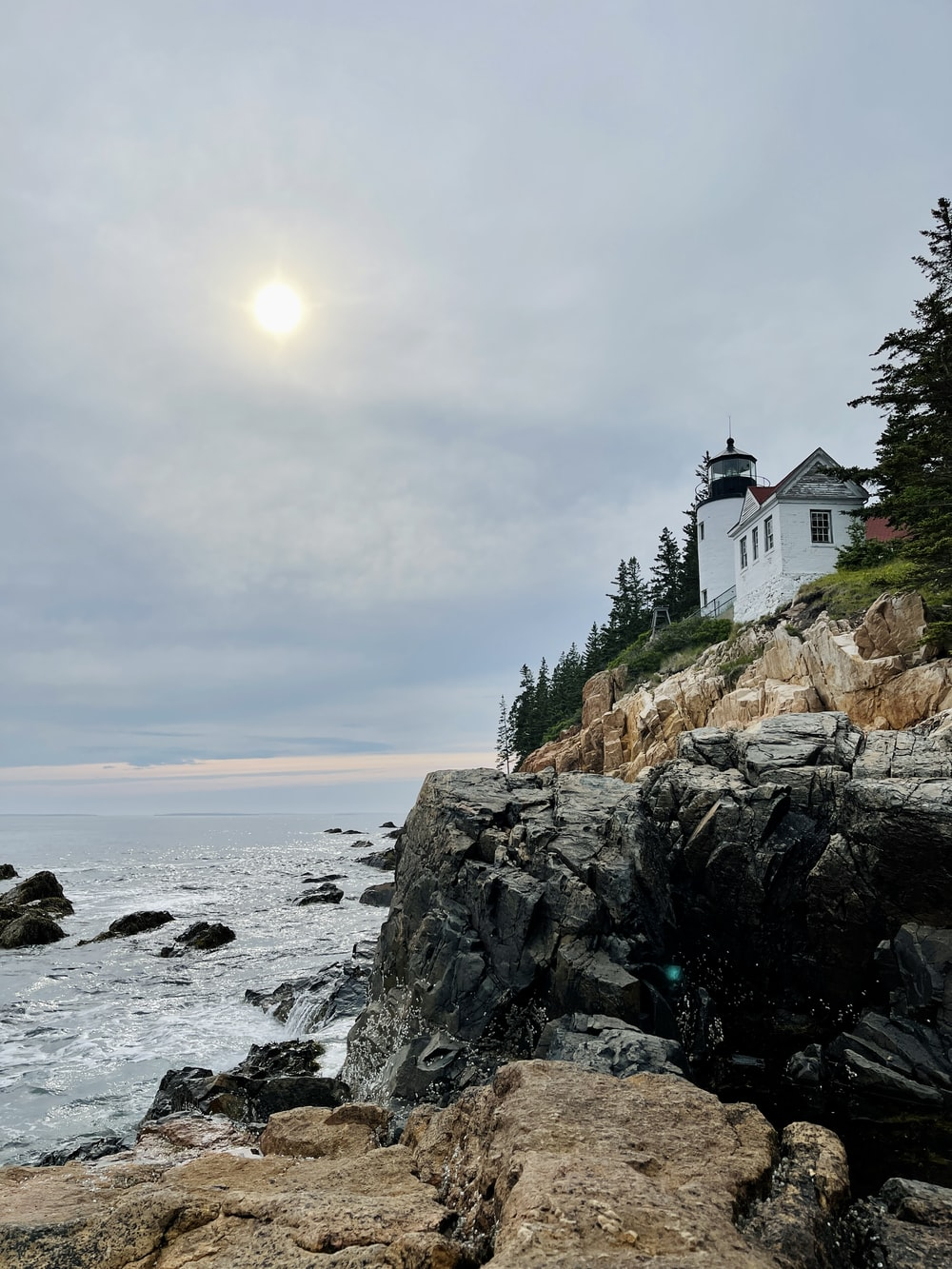 white and black house on rocky shore during daytime