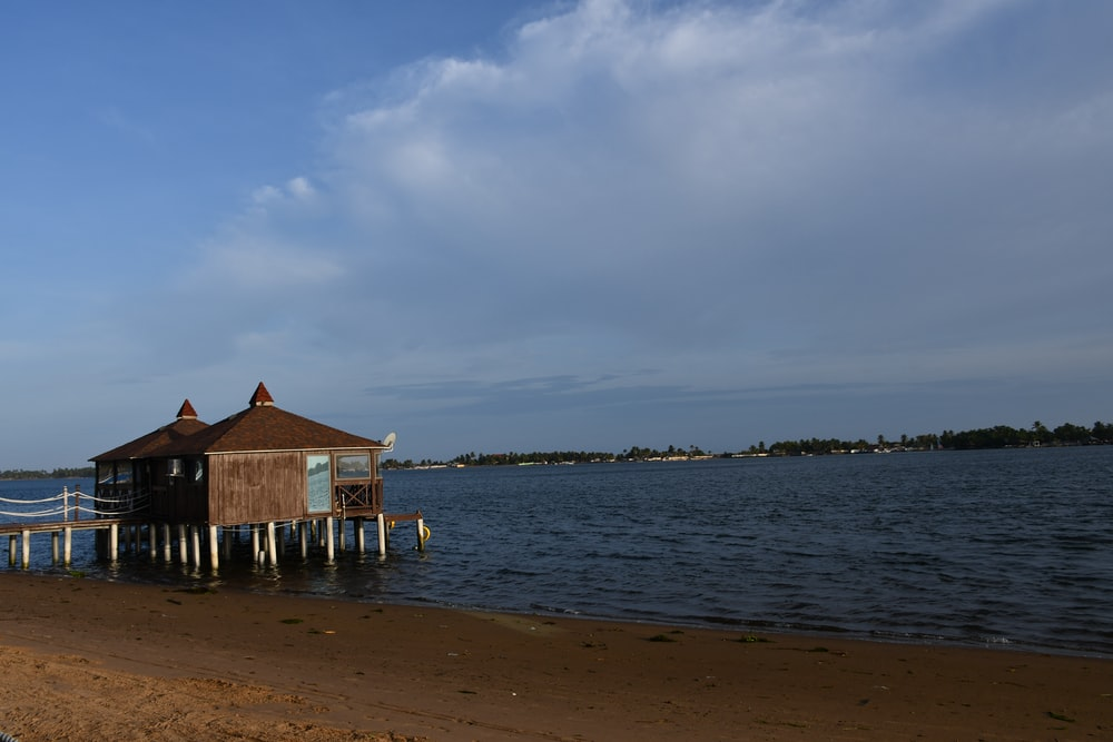 brown wooden house on sea shore during daytime