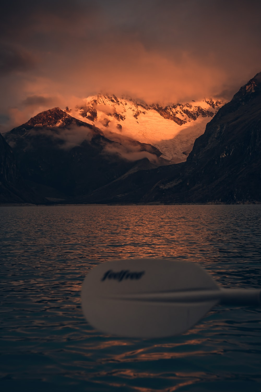 white surfboard on body of water near snow covered mountain during daytime