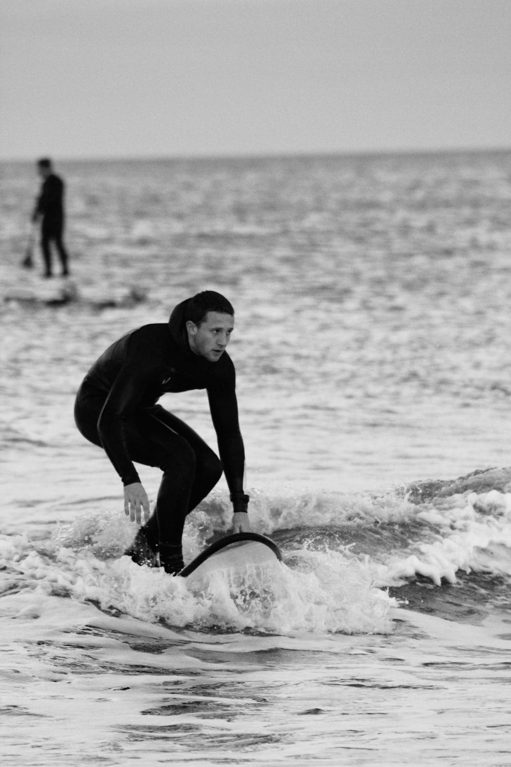 man in black wet suit riding on surfboard on beach during daytime
