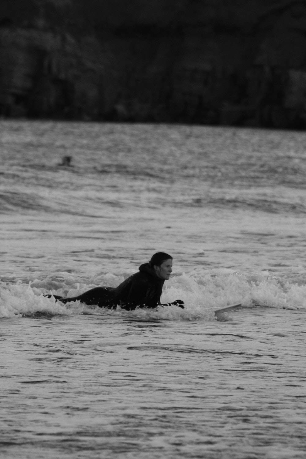 man in black wet suit lying on water during daytime