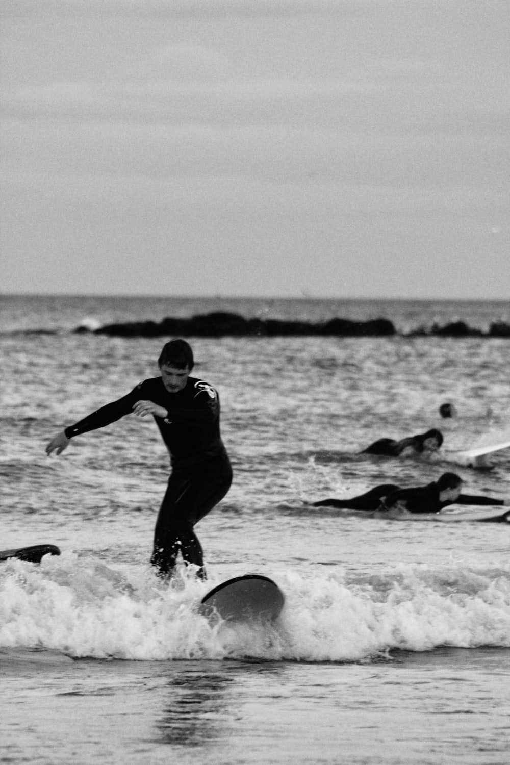 man in black wet suit playing on the beach