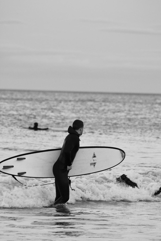 man in black wet suit holding surfboard on beach