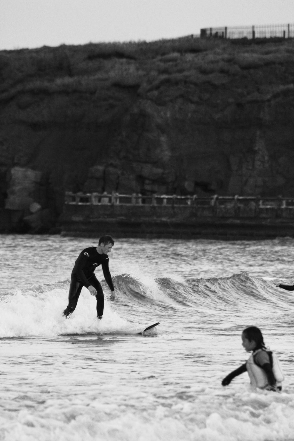grayscale photo of 2 boys playing on sea