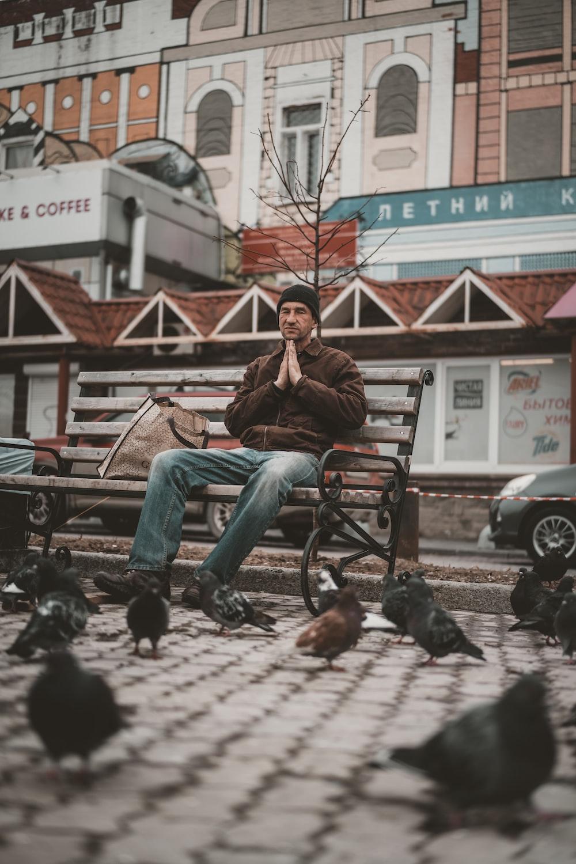 man in brown jacket sitting on brown wooden bench during daytime