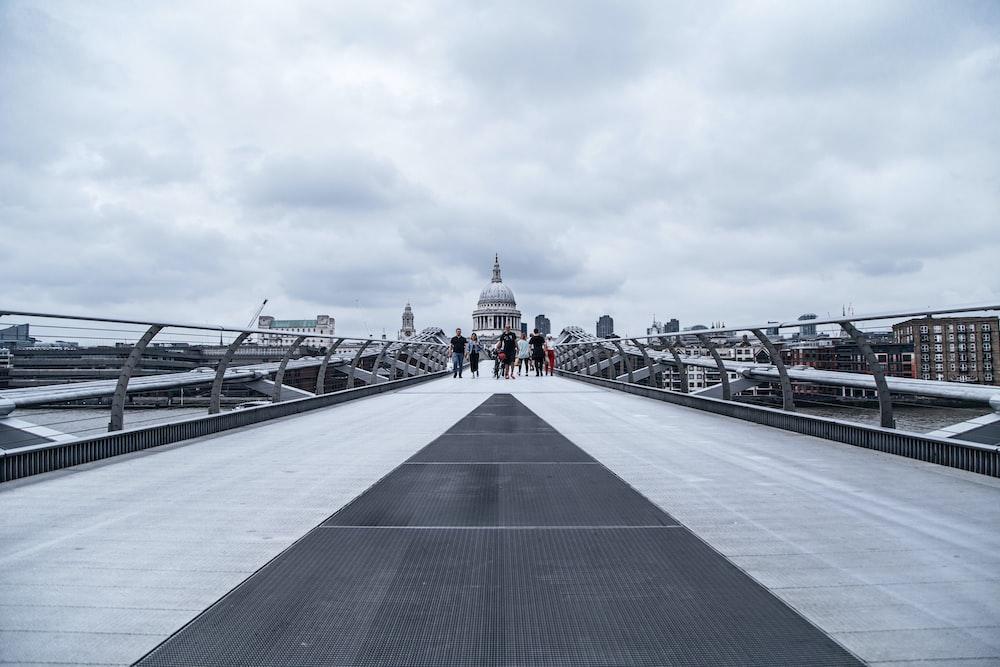 people walking on gray concrete bridge under gray sky during daytime