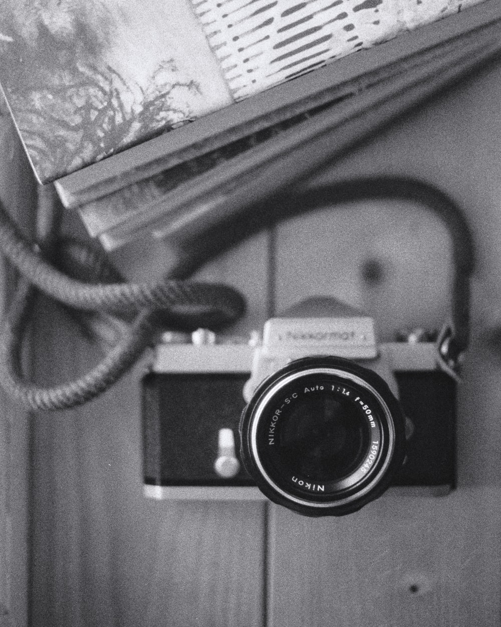 grayscale photo of a camera on a book
