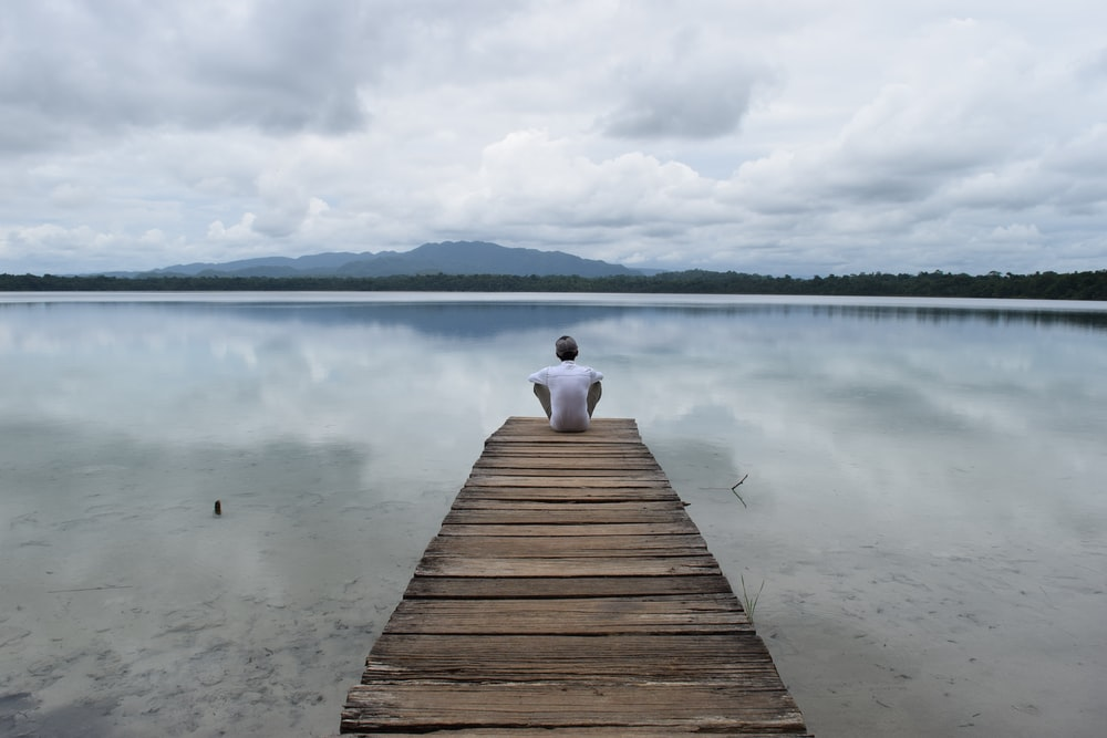 person sitting on wooden dock over the lake during daytime