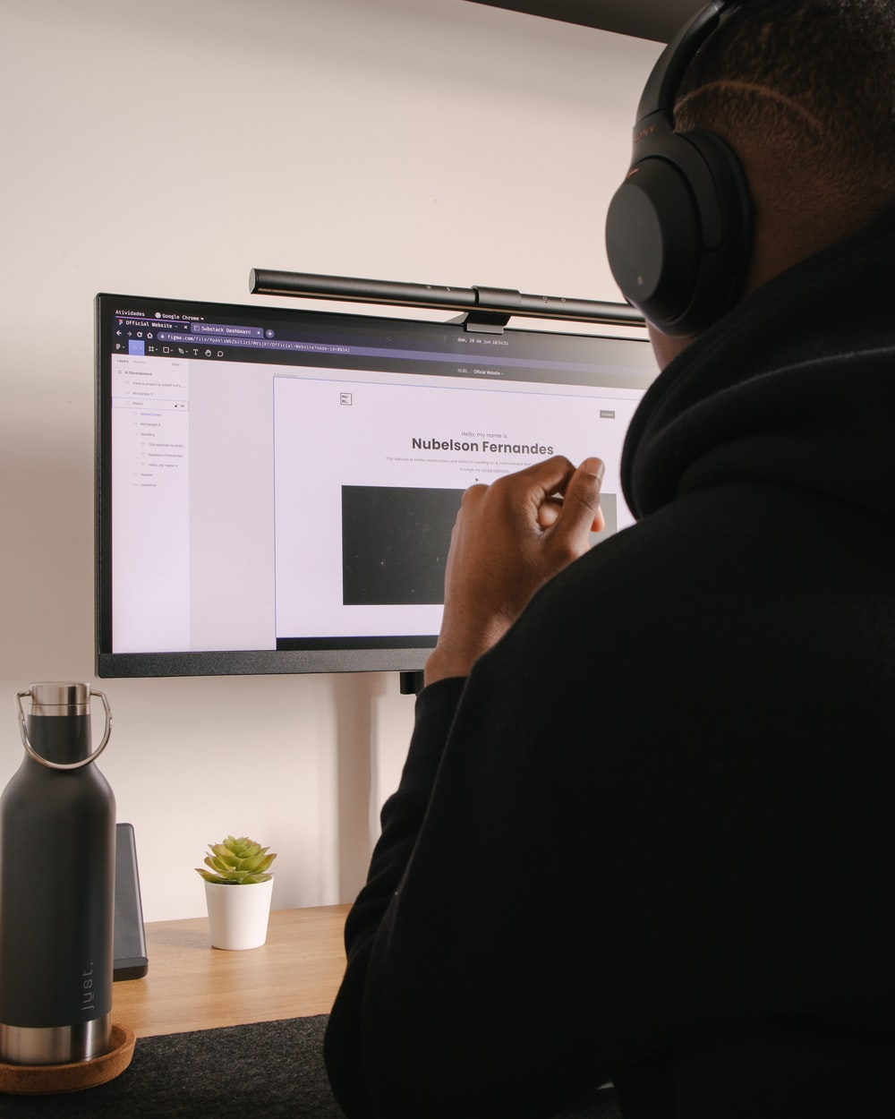 person in black hoodie sitting in front of black flat screen computer monitor