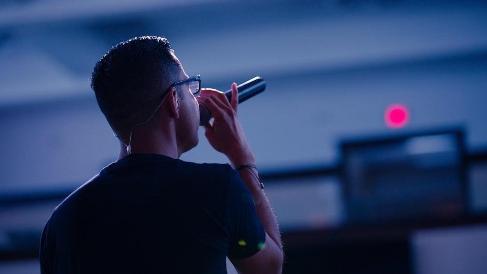 man in black crew neck shirt wearing black framed eyeglasses holding black smartphone