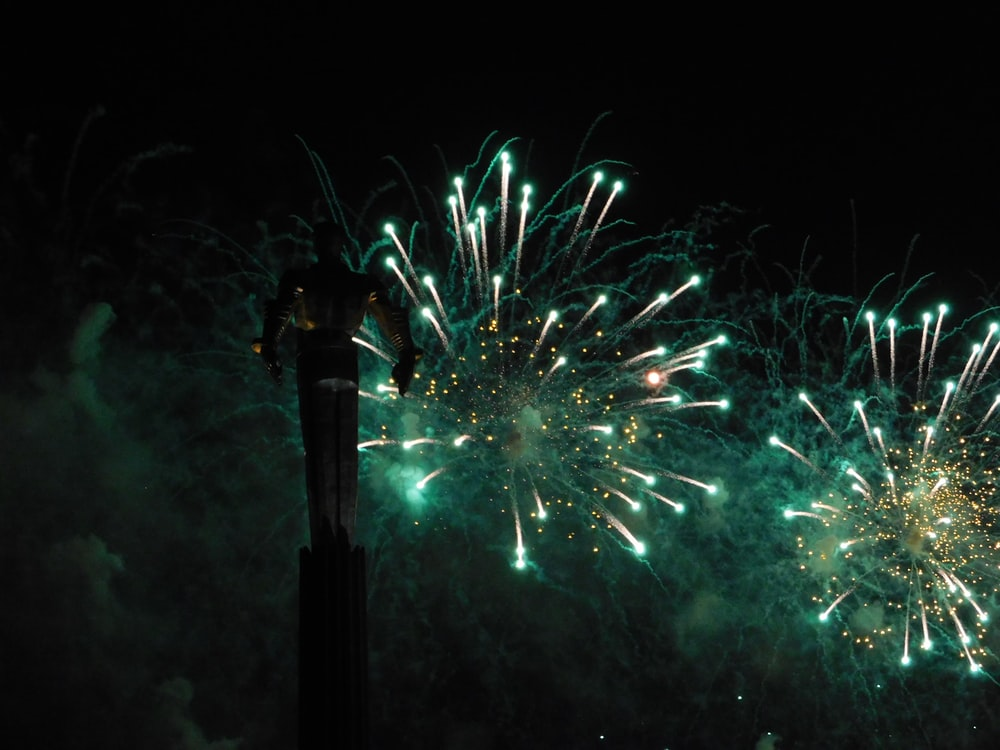 green and white fireworks display during nighttime