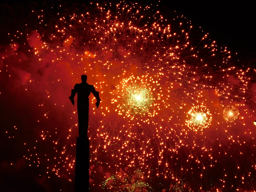 silhouette of man standing under fireworks during night time