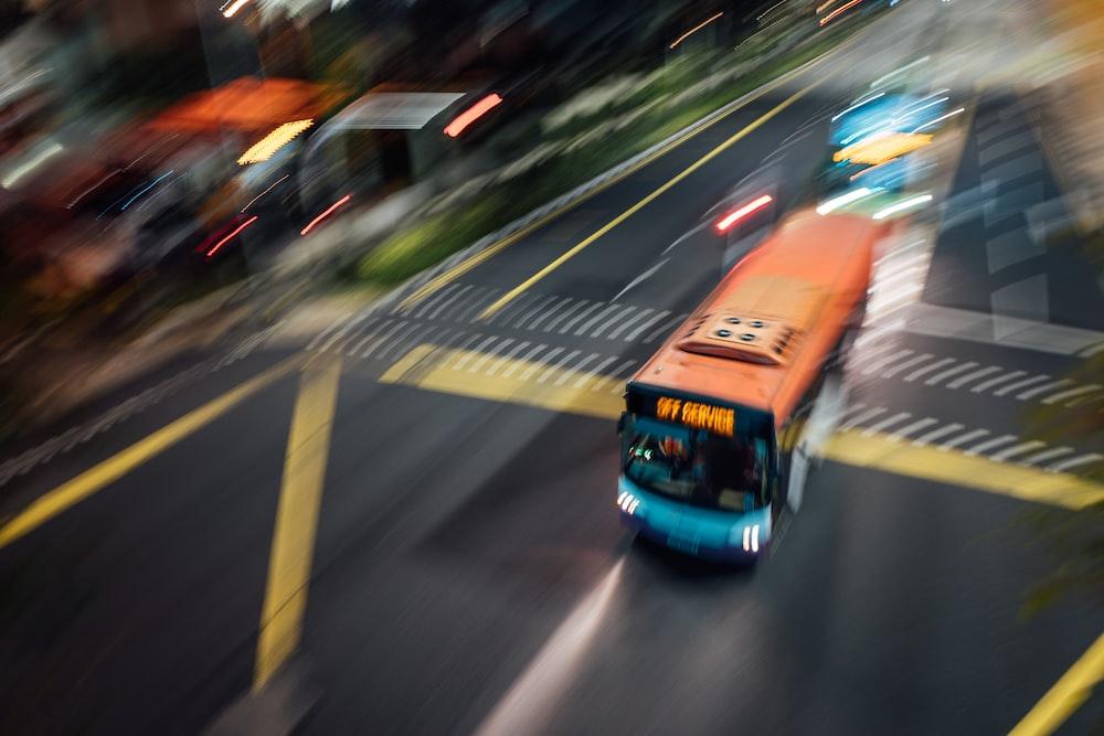 orange bus on the road during daytime