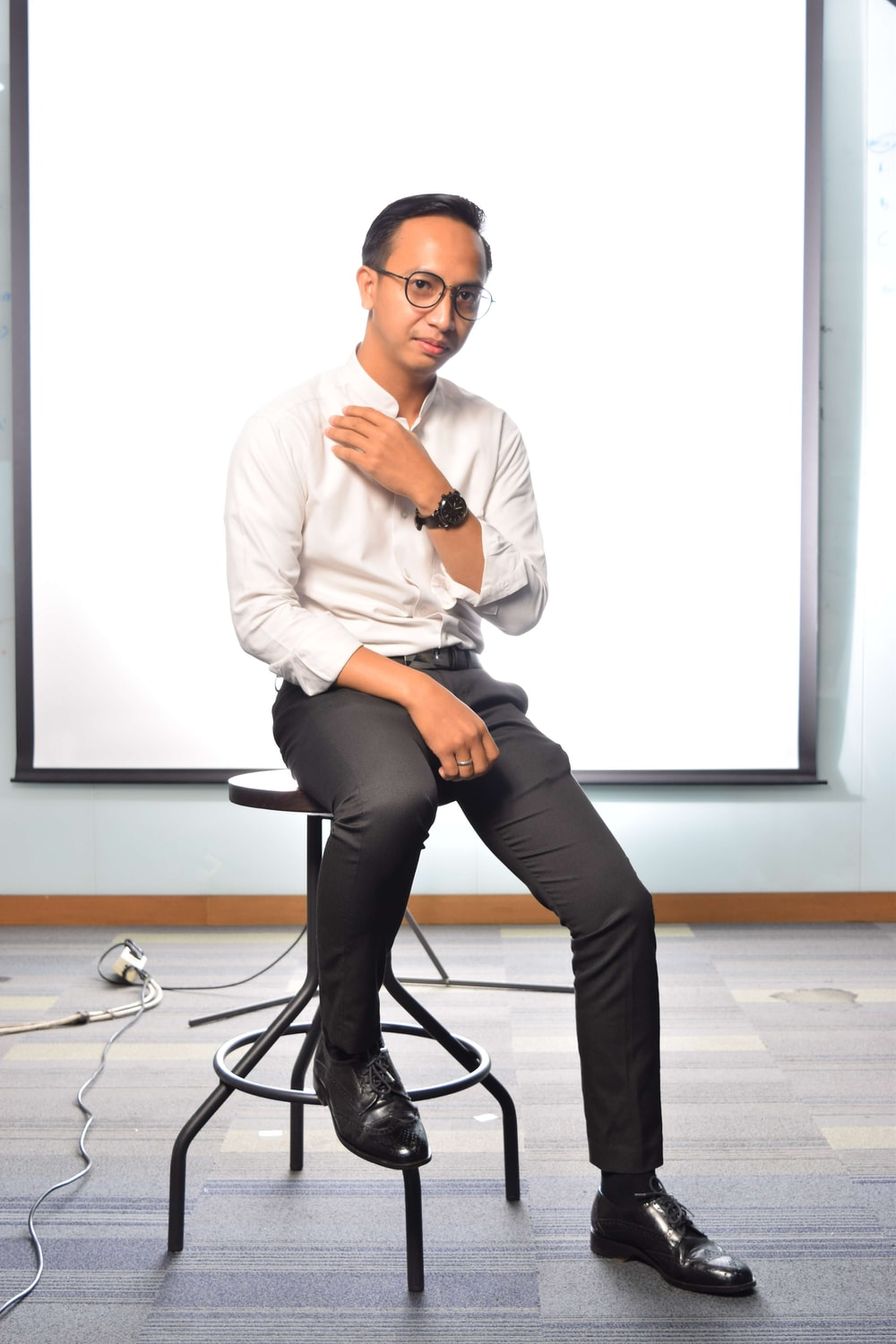 man in white dress shirt and black pants sitting on black rolling chair