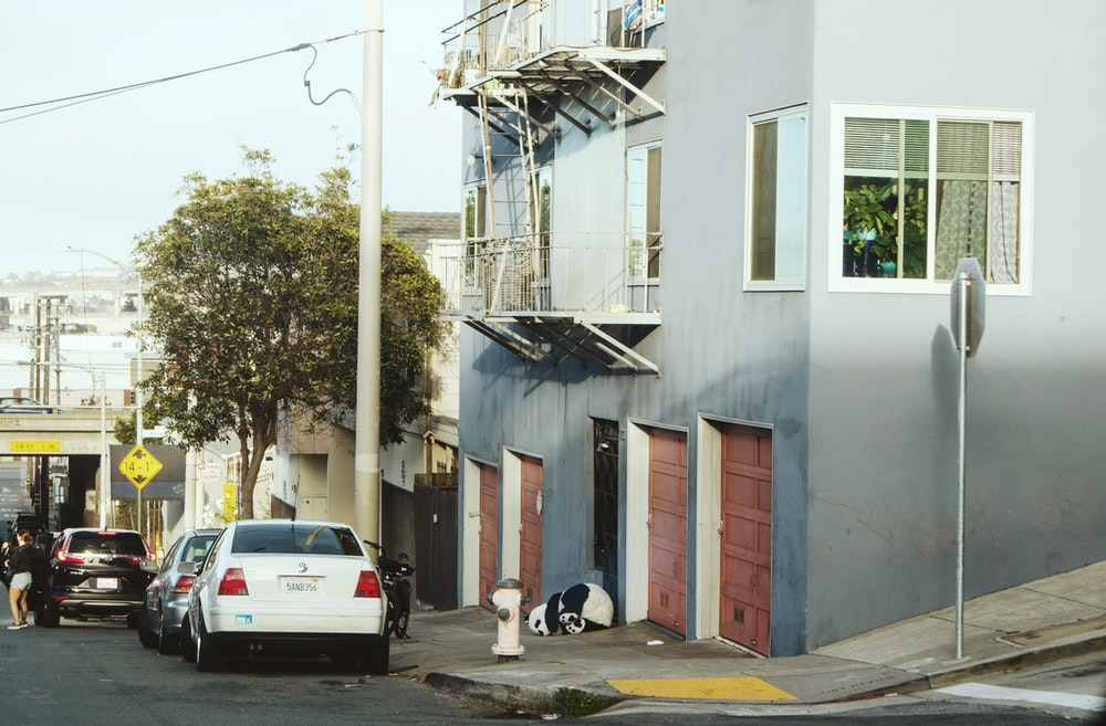 white car parked beside white building during daytime