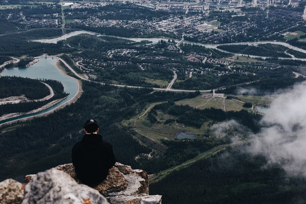 man in black jacket sitting on rock looking at the city during daytime