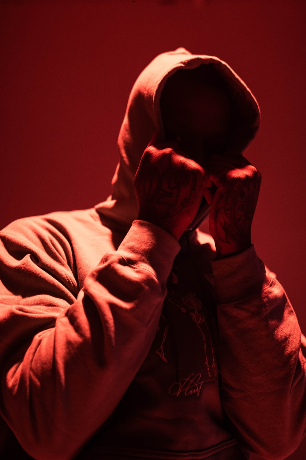 man in hoodie covering his face