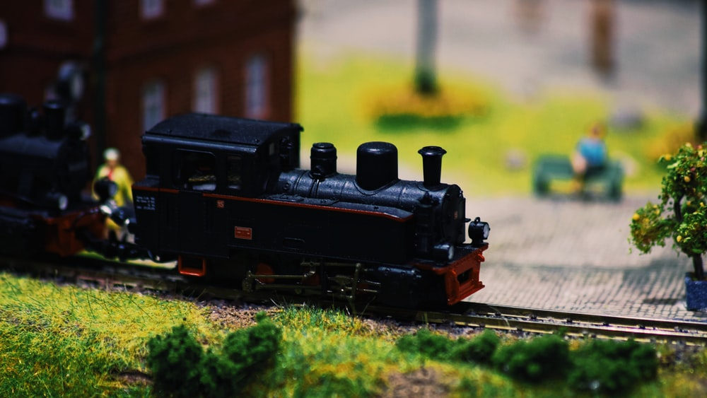 black and red train toy on rail tracks