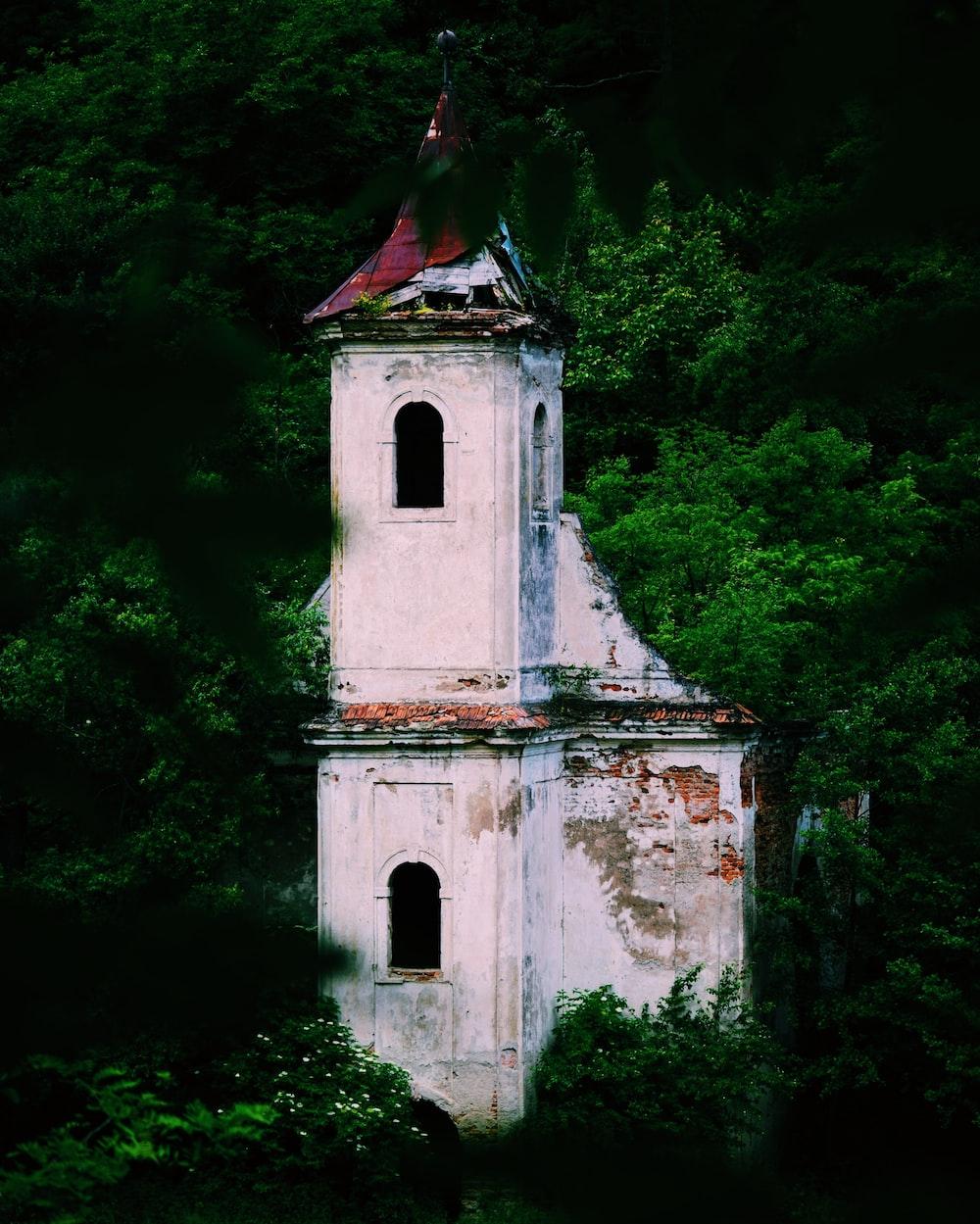 white concrete church near green trees during daytime