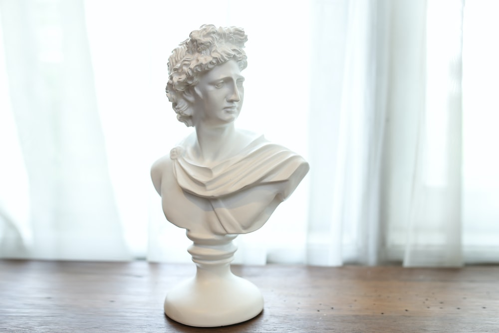 white ceramic statue on brown wooden table