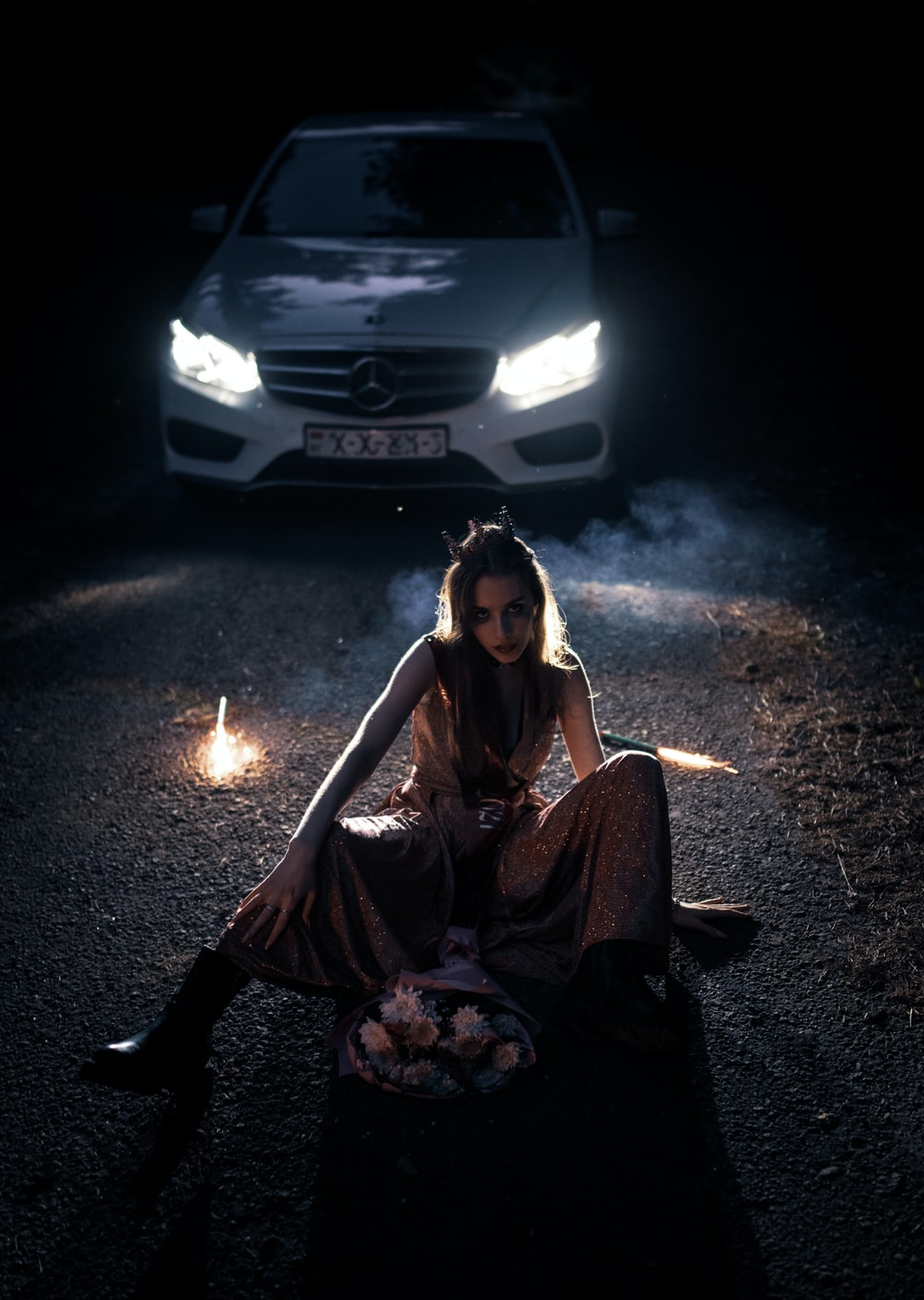 woman in brown long sleeve shirt sitting on ground beside white car during nighttime