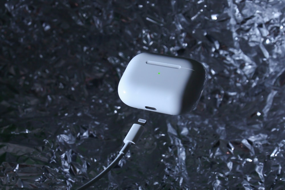 white charging adapter on black and gray surface