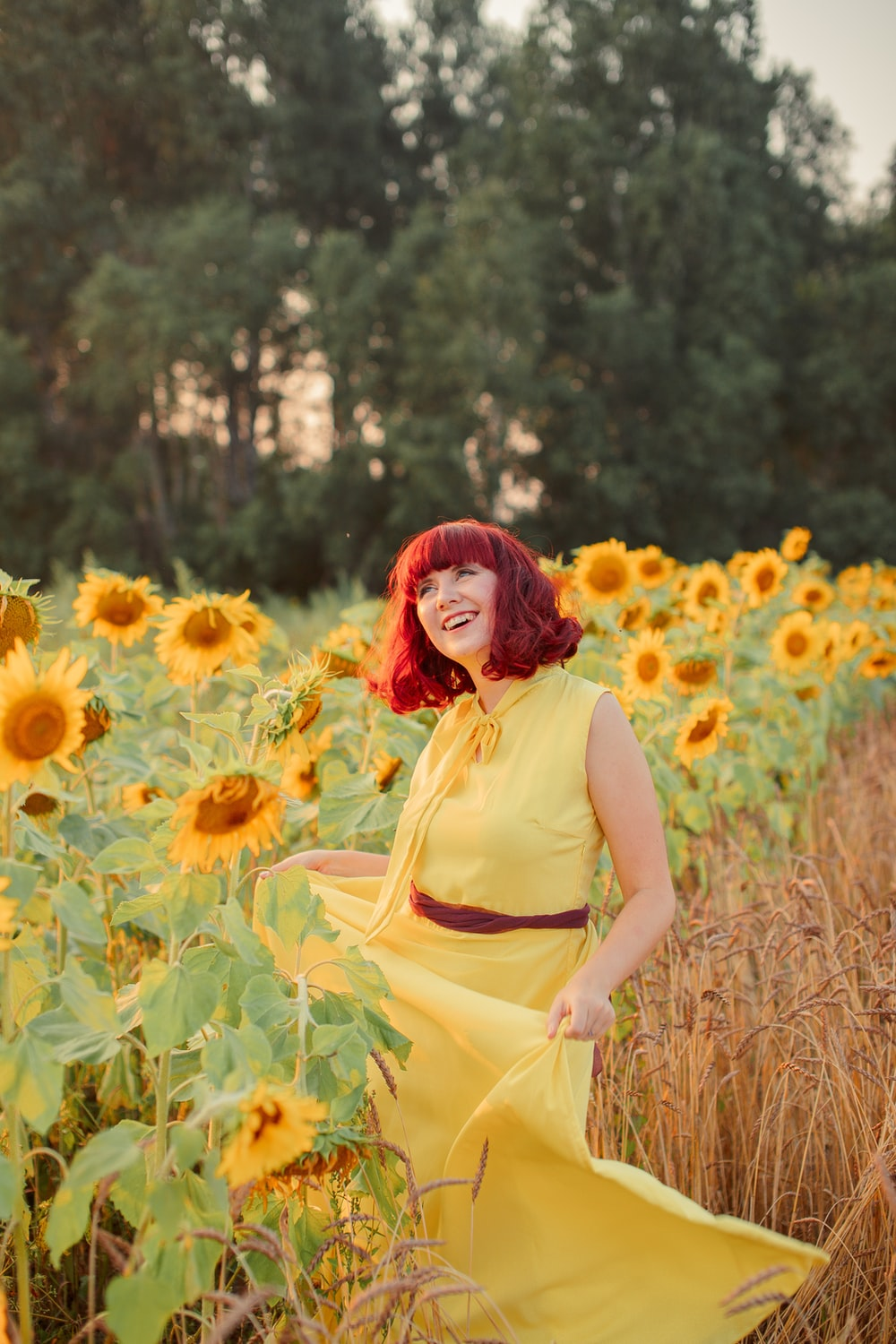 woman in yellow sleeveless dress standing on sunflower field during daytime