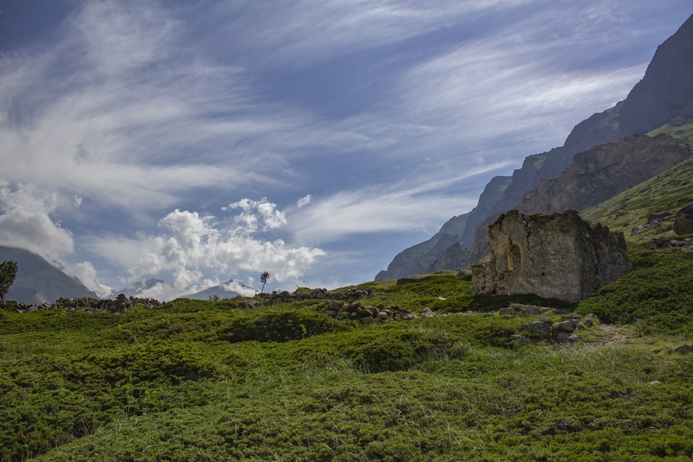 green grass field near brown rock formation under white clouds and blue sky during daytime