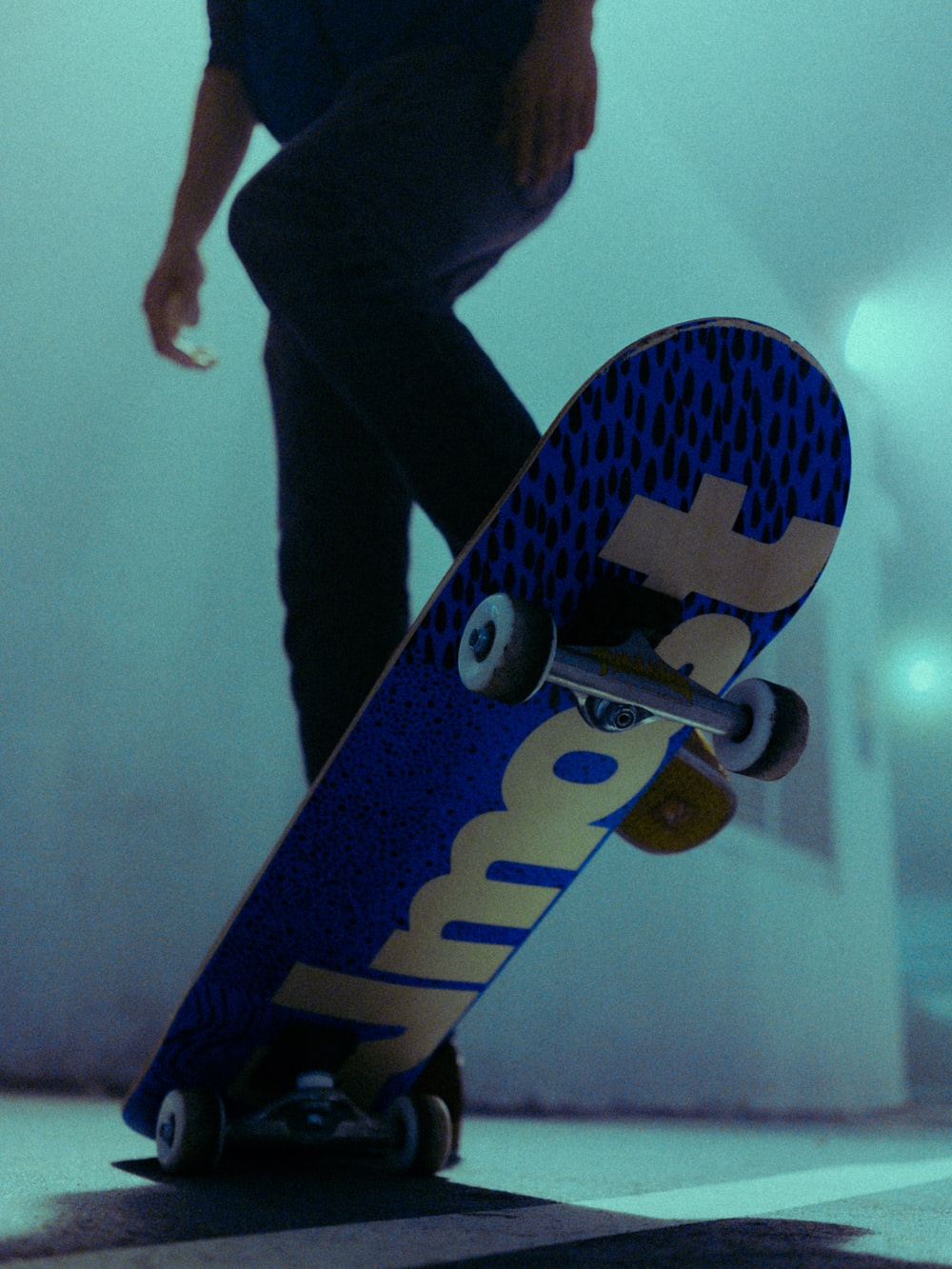 person in black pants standing on blue and white skateboard