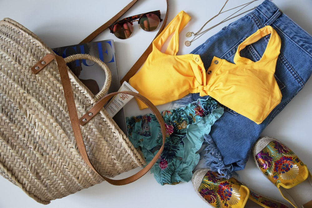 blue denim jeans beside yellow leather handbag