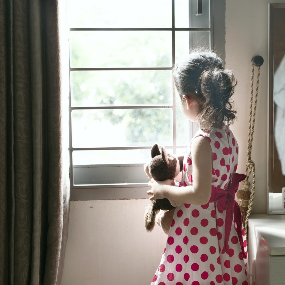 girl in red and white polka dot dress standing beside window