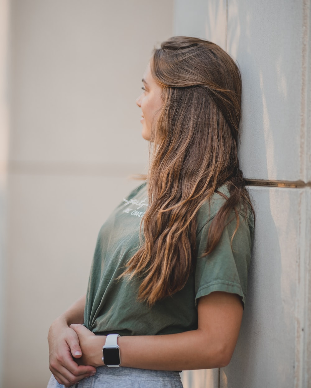 woman in green shirt leaning on white wall