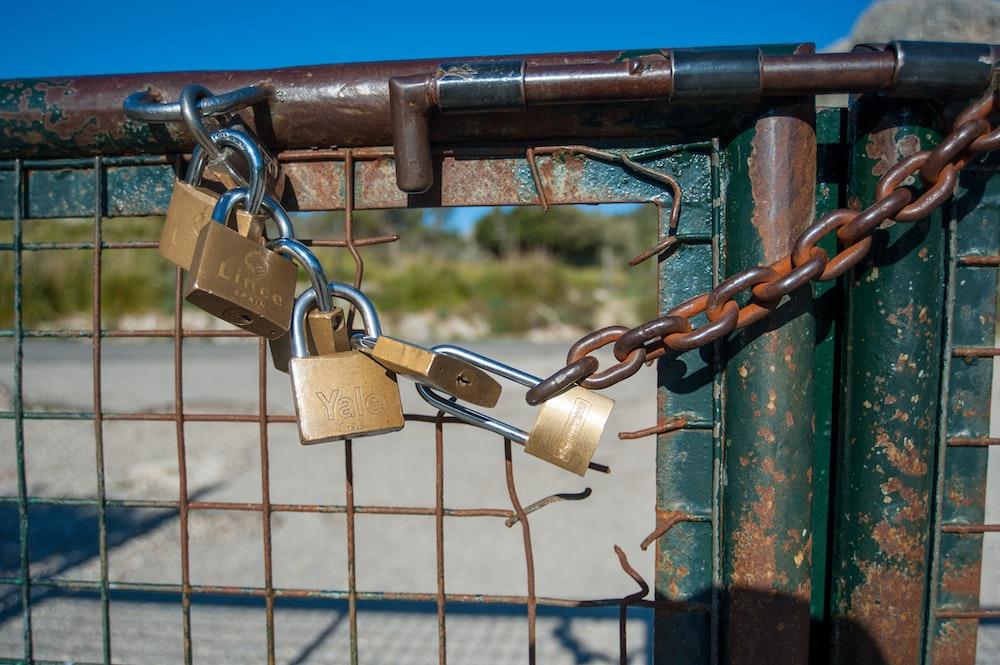 brass padlock on blue metal fence