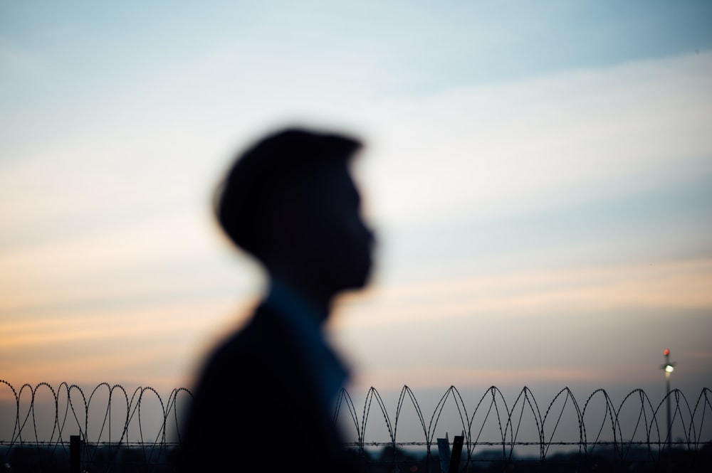 silhouette of man standing near fence during sunset