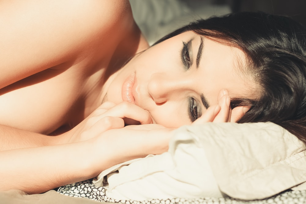 topless woman lying on bed