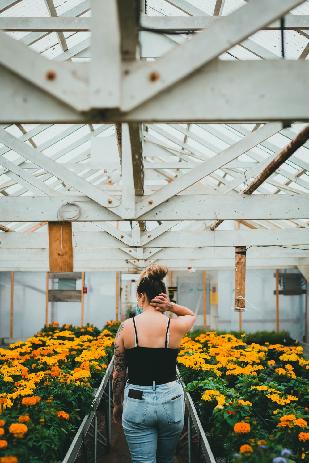 woman in black spaghetti strap top standing on yellow flower field during daytime