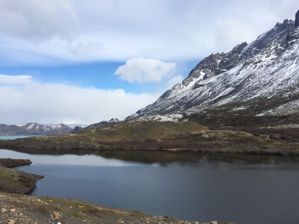 lake near snow covered mountain during daytime