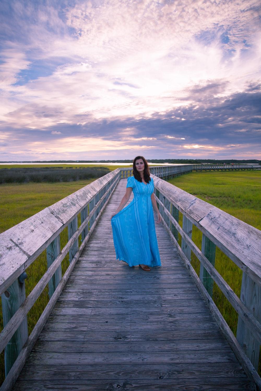 woman in blue dress standing on wooden bridge