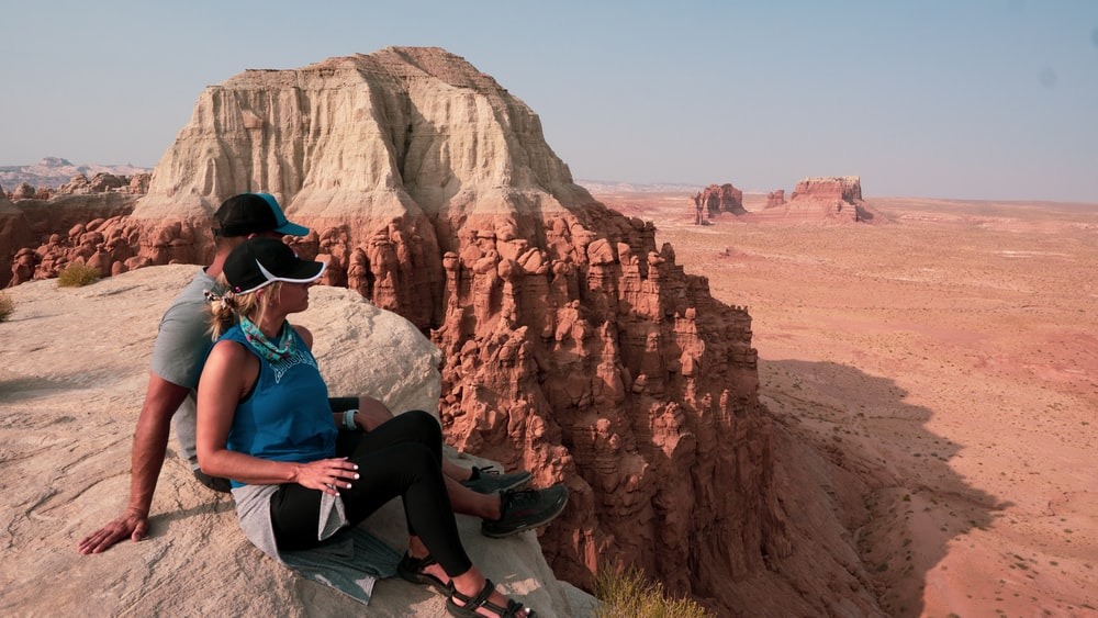 man in blue shirt and black pants sitting on rock formation during daytime