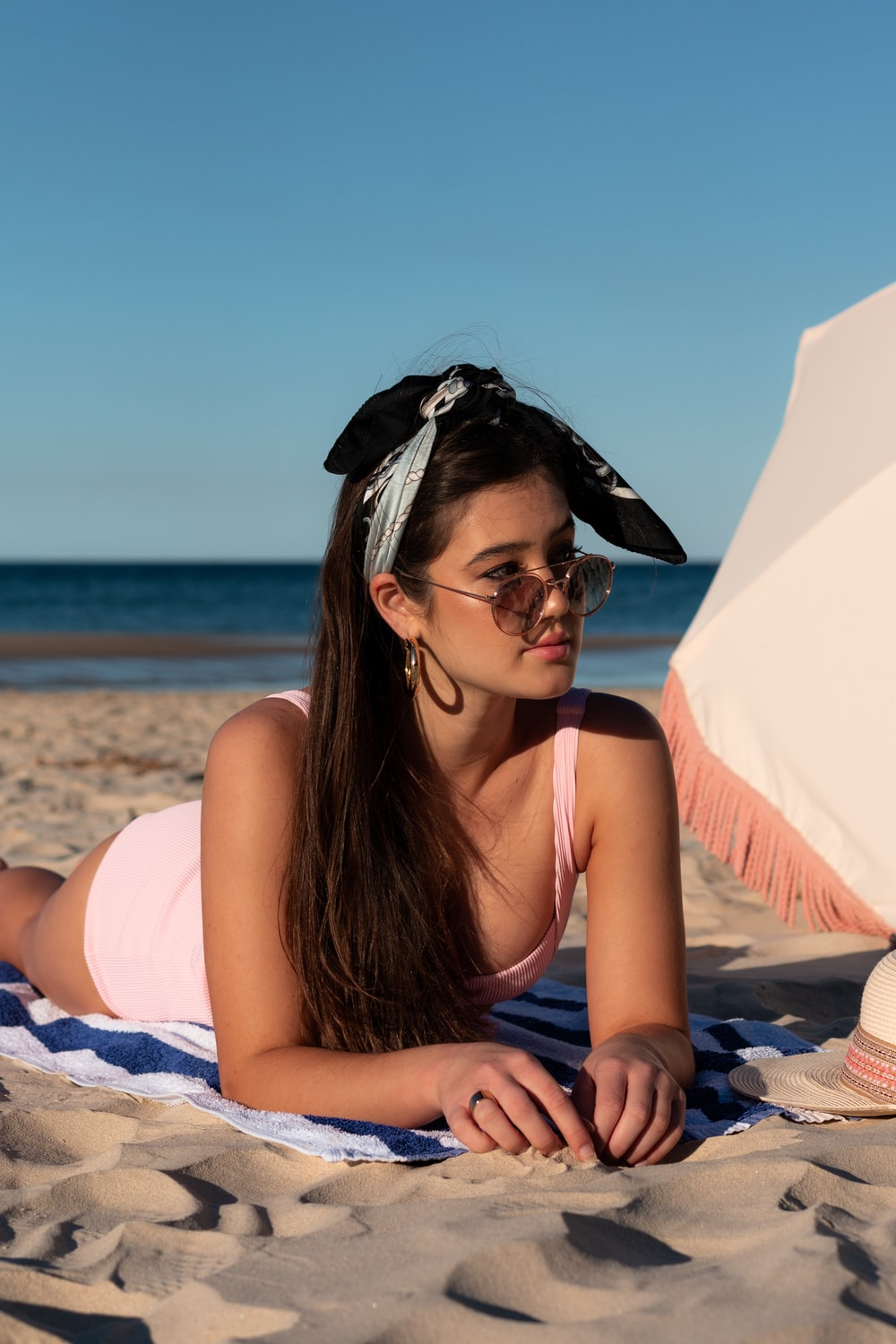 woman in pink tank top sitting on white textile on beach during daytime