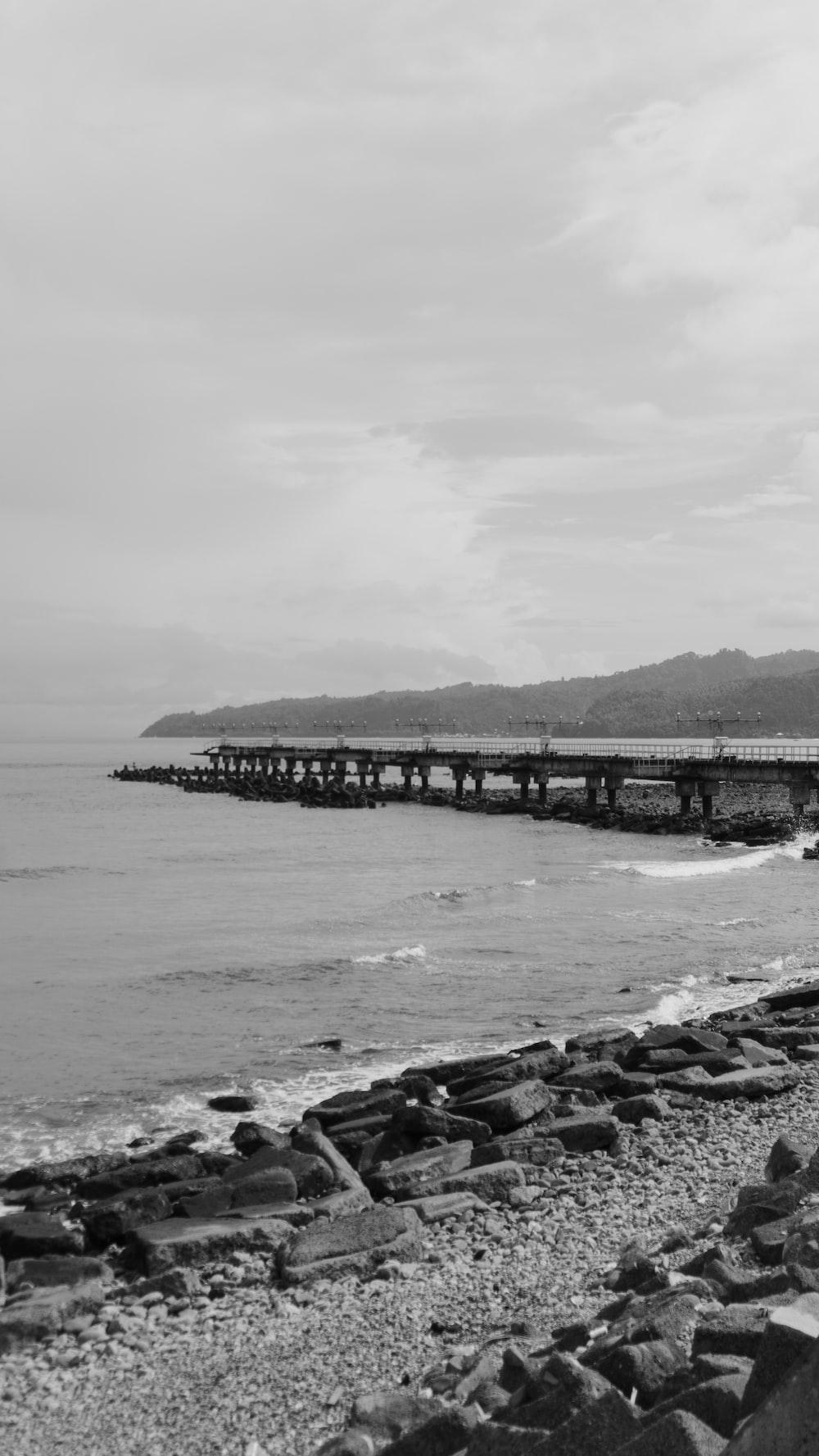 grayscale photo of bridge over the sea