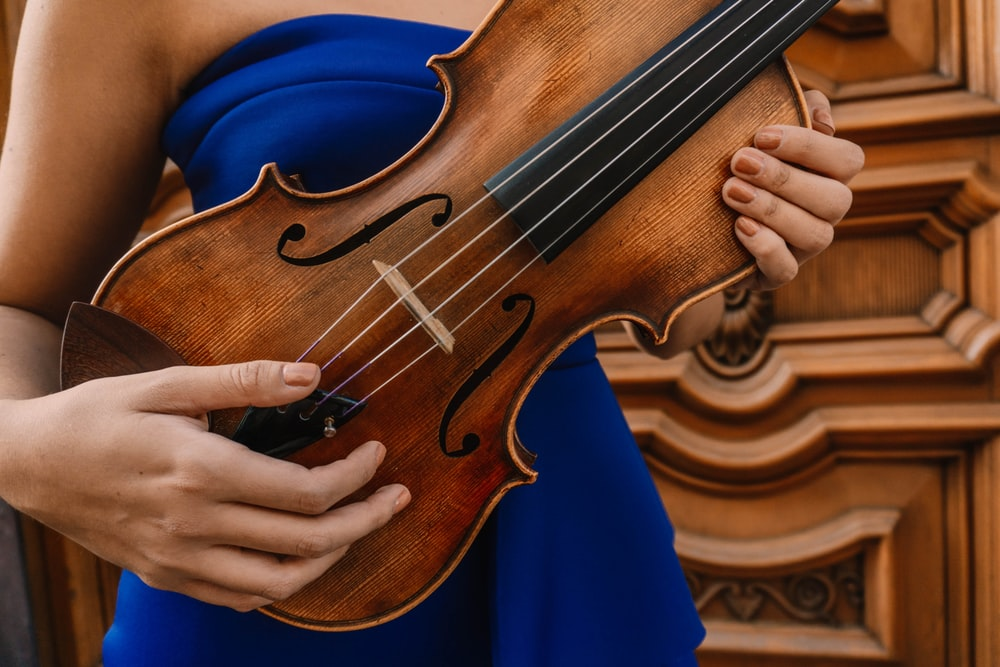 person playing brown violin during daytime