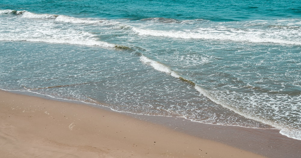 blue ocean waves on brown beach shore during daytime