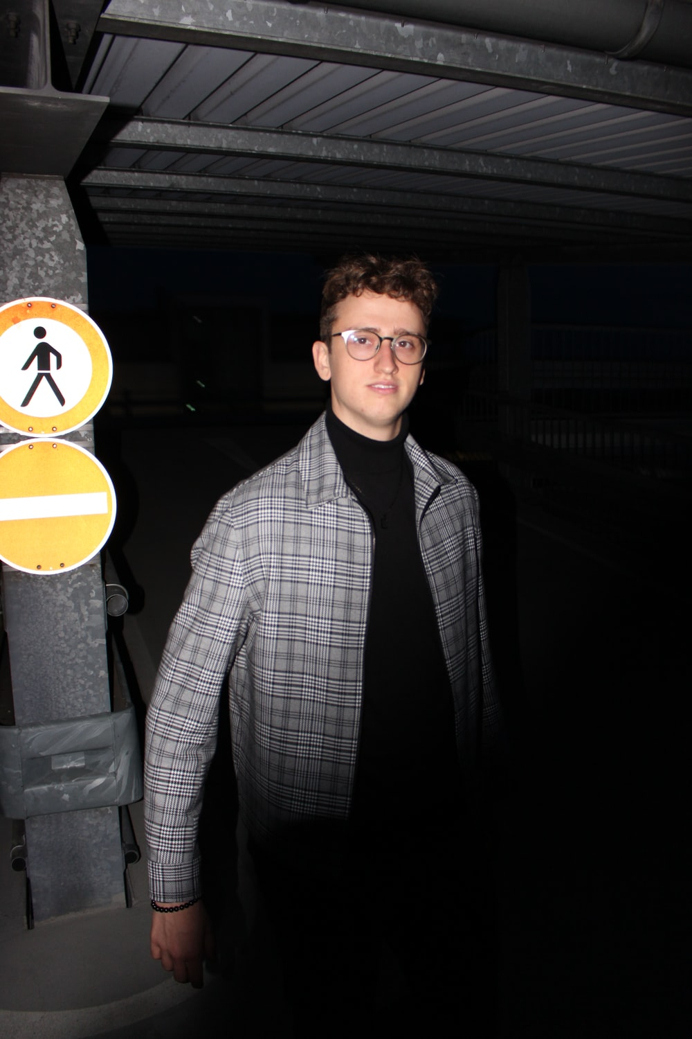 man in black suit jacket standing beside yellow and black no smoking sign