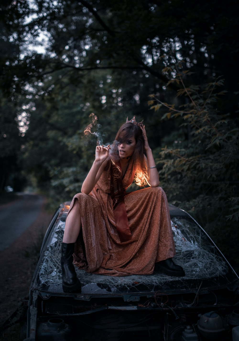 woman in red dress sitting on black car hood during daytime