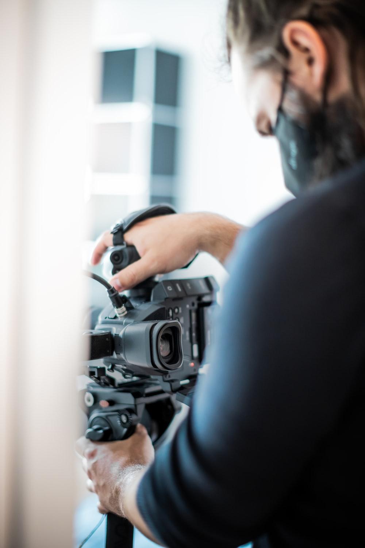 man in black shirt holding black dslr camera