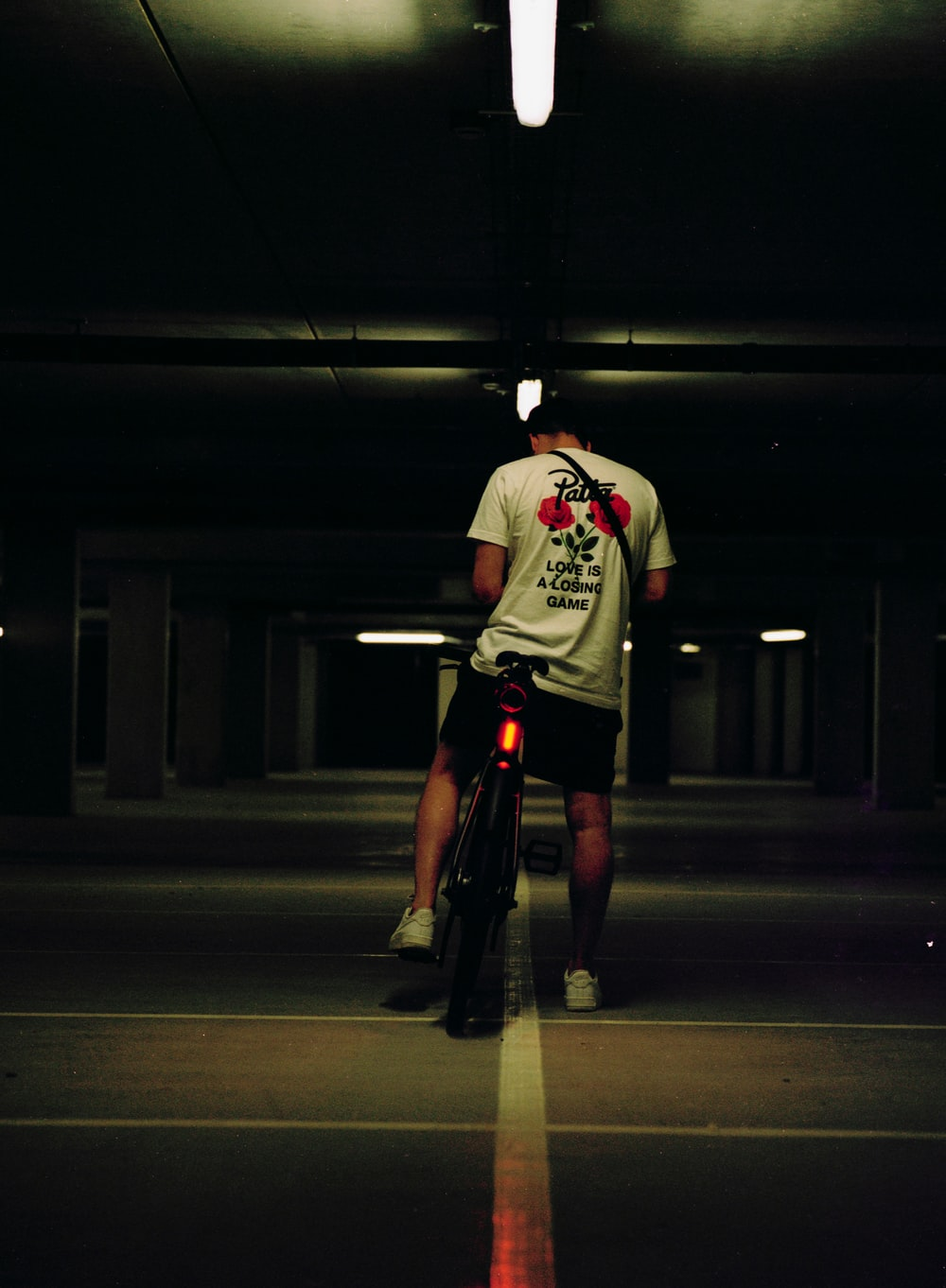 man in white and red crew neck t-shirt and black shorts riding bicycle