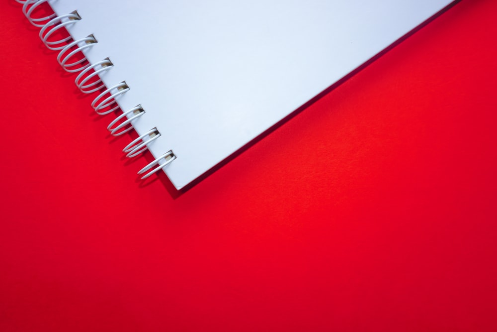 white spiral notebook on red surface