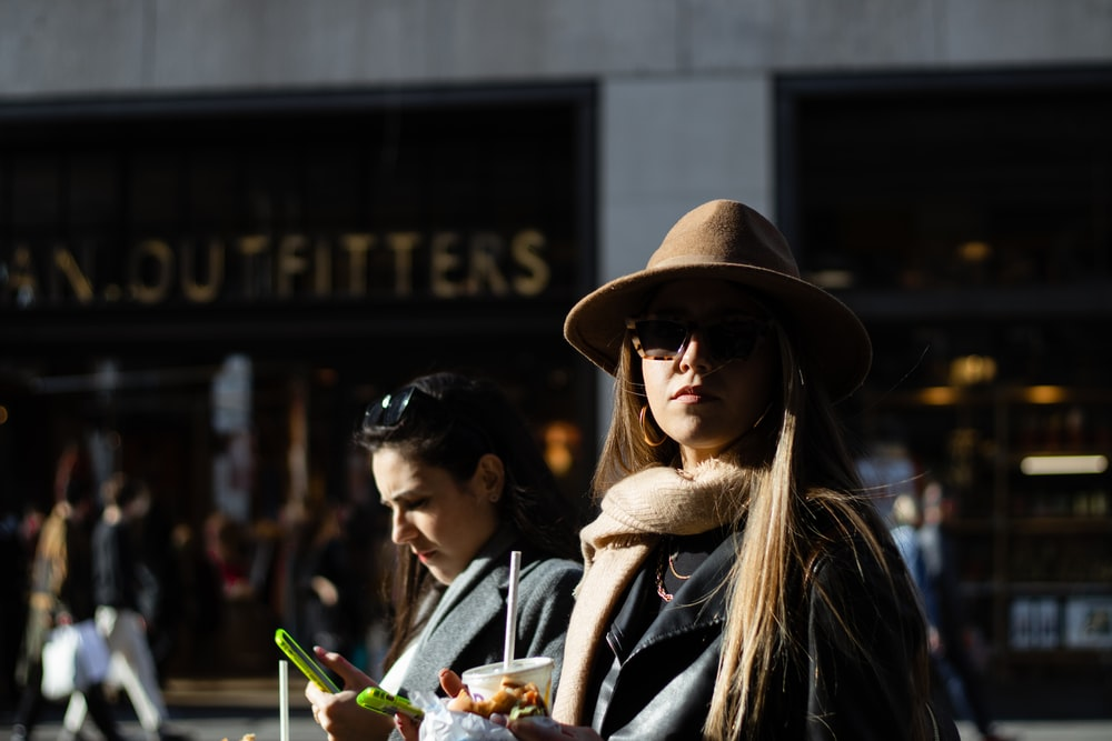 woman in black and white striped long sleeve shirt and brown hat holding green smartphone during