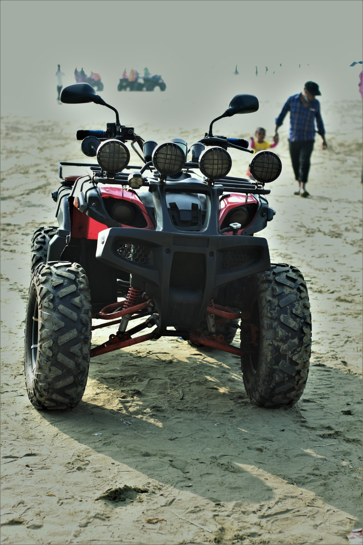 black and red atv on white sand during daytime